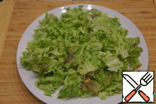 Pick the lettuce leaves with your hands, put most of them on a flat dish, covering the entire bottom. Pour the rest into a deep bowl.