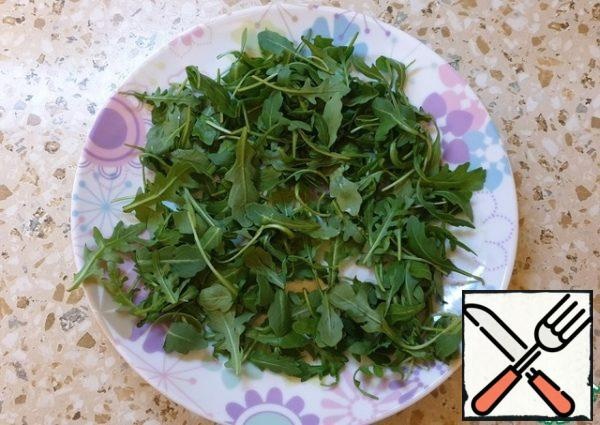 We collect the salad. Place the arugula on a plate.