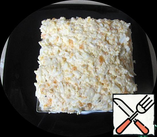 We put the form for the salad on a flat plate and spread the first layer of squid with mayonnaise. Spread the onion on top, add a little salt and grease it with mayonnaise.