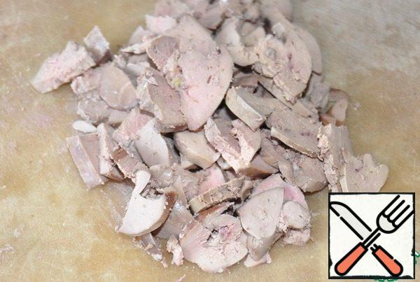 Chicken liver is boiled for 10 minutes in salted water. Let it cool. Cut into thin slices.