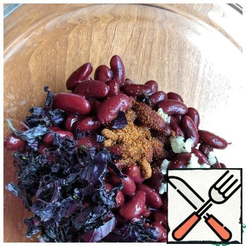 Drain the liquid from the beans. Pass the garlic through a press, finely chop the basil. Add salt and adzhika.