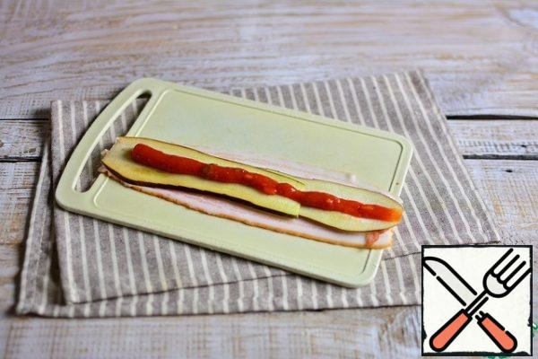 On 2 strips of bacon (next to it, so that it is wider), spread 2 strips of eggplant along the entire length of the bacon. Top with a strip of ketchup.