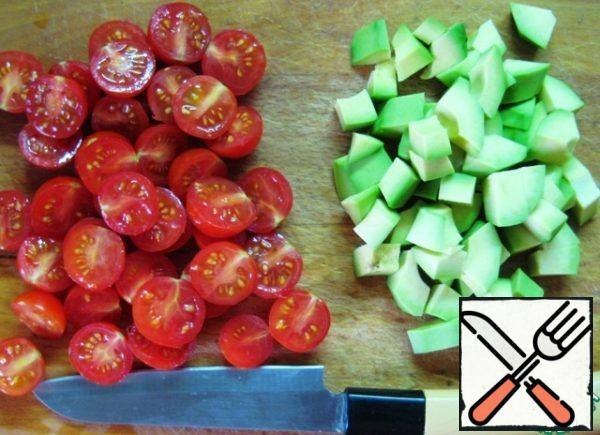 Cut the cherry tomatoes in half, peel the avocado and cut into small pieces.