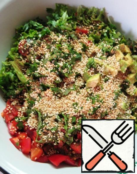 Add the sesame seeds to the salad, season with olive oil and mix gently.