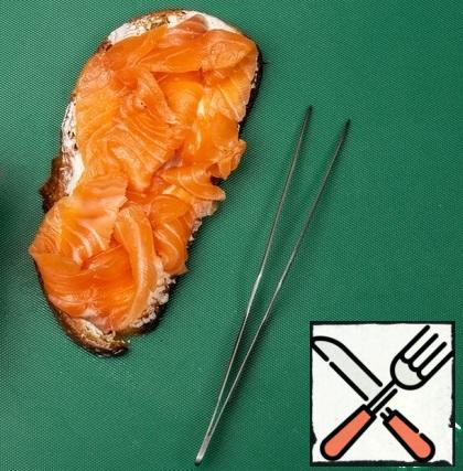 Lightly salted salmon cut into thin slices, carefully roll up and put on the cheese.