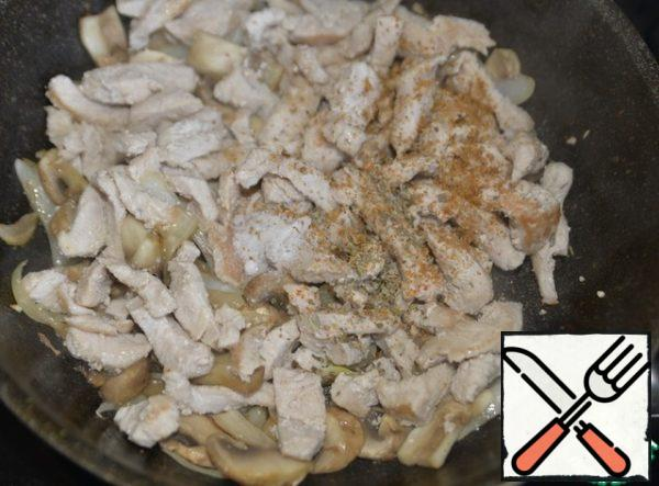 Return the fried turkey to the pan. We put salt, a mixture of peppers, Provencal herbs. Mix it up.