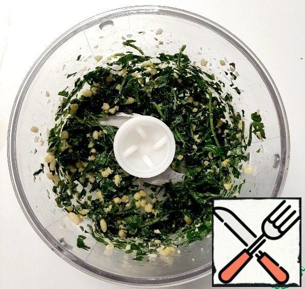 Place the washed and dried parsley without large stalks in the bowl of a blender. Add 2 tablespoons of pine nuts and a clove of garlic. Grind it.