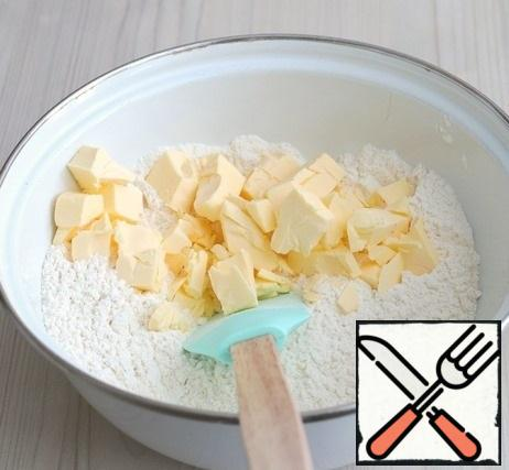 Next, add the cold butter, cut into cubes. Chop the flour and butter into butter crumbs.