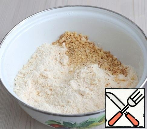 Add walnuts to the butter crumbs. Mix the mixture.