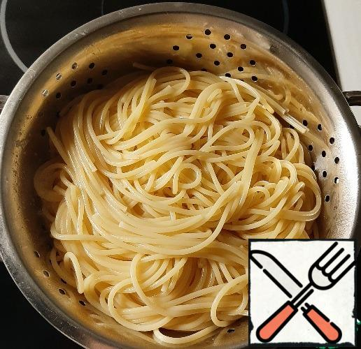 Boil the spaghetti in salted water, toss in a colander, return to the pan, pour over the olive oil, and mix.