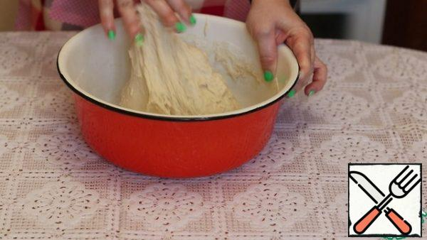 In the sifted flour, add salt, sugar, yeast, and butter. Mix thoroughly, pour water and knead the dough. It will be a little liquid and will stick to your hands a little.