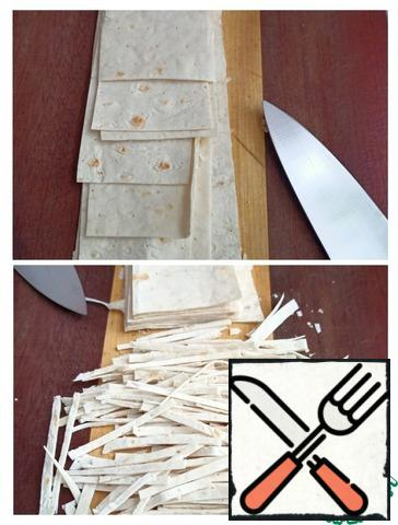 We cut the pita bread into strips 7-8cm wide, and chop the strips across into noodles.
