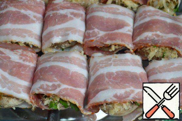 Wrap each cap with a strip of bacon, put it in a baking dish and send it to a preheated 180*C oven for 15 minutes.