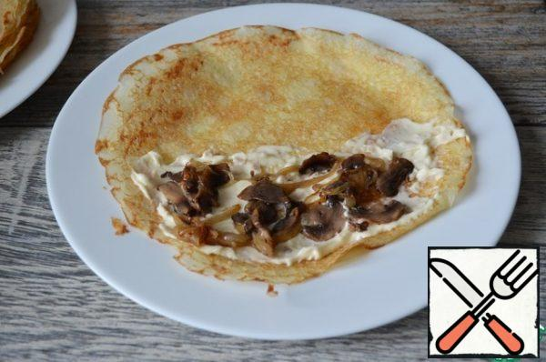 Half of the pancake spread with cheese, put the mushroom mixture.