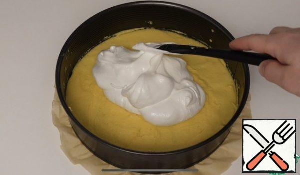 In a baking dish of 26 cm, spread the baking paper on the bottom, then spread the sponge dough, spread it well on the bottom, spread the meringue well on top