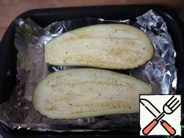 Wash and dry the eggplant with a paper towel, cut into two halves, and sprinkle with olive oil. Then sprinkle with salt and ground black pepper to taste. Spread on the foil with the skin down and bake for 20 minutes. Cool the finished eggplant and peel it.
