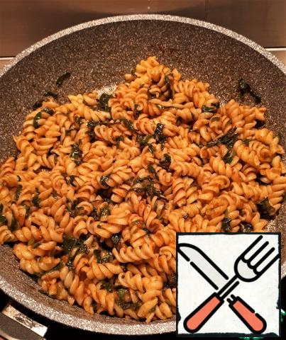 Transfer the folded spirals to the frying pan, add half a ladle of water from under the pasta, mix everything well and warm it up for another 2-3 minutes, stirring occasionally.