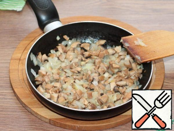 Prepare the filling. Fry the diced onion in preheated vegetable oil until transparent. Add finely chopped mushrooms, spices and salt, fry for 5 minutes, not forgetting to mix periodically.