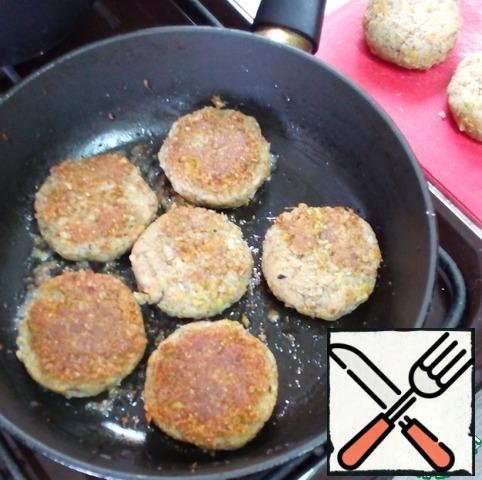 In a non-stick frying pan, where the frying was previously prepared, put one clove of garlic, crushed with a knife, add a small amount of vegetable oil, warm up the pan. Remove the garlic. Put the cutlets in a frying pan and fry until browned on both sides. While the cutlets are cooking, boil the tricollini in salted water with the addition of 1 tbsp. l. vegetable oil.