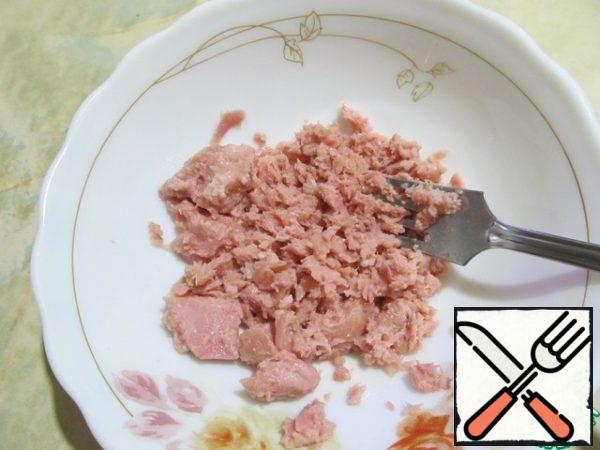 Put the tuna slices in a bowl and mash with a fork.