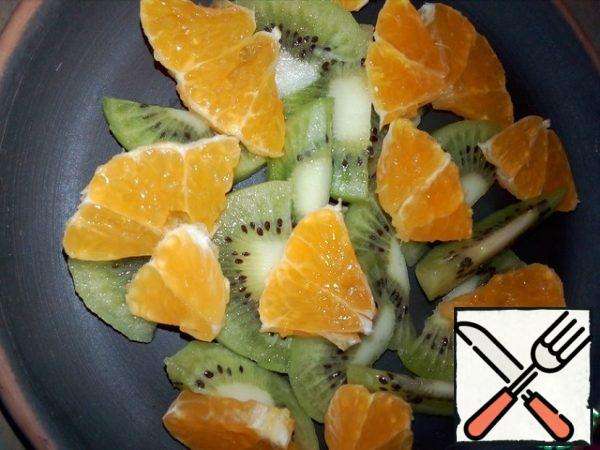 Cut the tangerine into small pieces. Place the kiwis and tangerines on a plate.