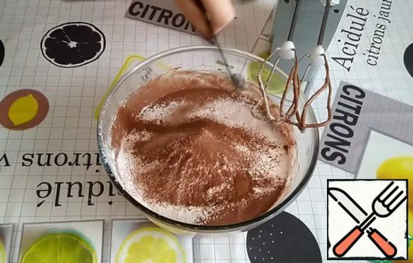 Add the orange zest, ground hazelnuts. Sift the flour together with baking powder and cocoa powder. In addition, add ground allspice, cinnamon, nutmeg.
