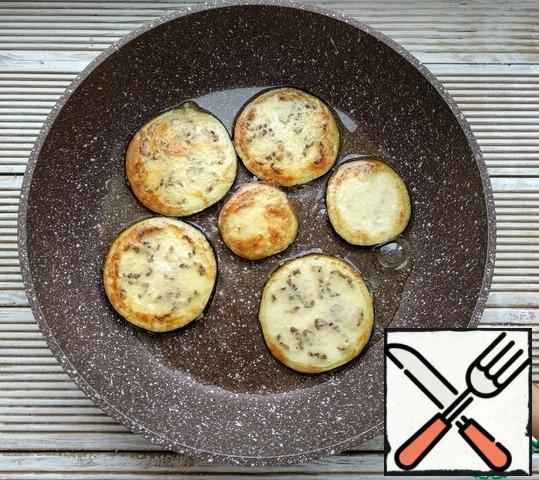 Fry the eggplant rings in vegetable oil on both sides until golden brown. Put the eggplant on paper napkins to absorb the excess oil.