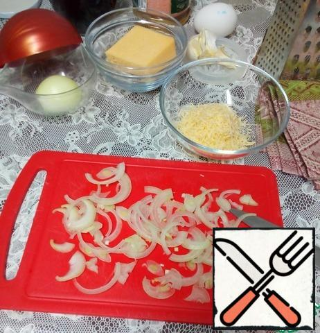 To spread the bread, prepare the cheese and onion mass. Cut half of the onion into thin half-rings, brown in a non-stick frying pan with a pinch of sugar for caramelization. Grate the cheese on a fine grater, mix with the caramelized onion and mayonnaise sauce. You can add one crushed garlic clove for a more spicy snack.