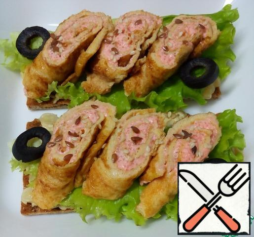 Put three egg and fish rolls on each loaf, decorate with rings of olives, sprinkle with flax seeds and sesame seeds. Bon Appetit!