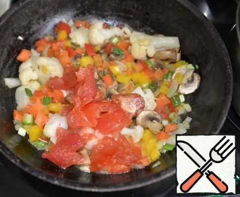 Scald the tomato, remove the skin, cut into cubes and put it with the vegetables, mix. Simmer for 2 minutes over medium heat.