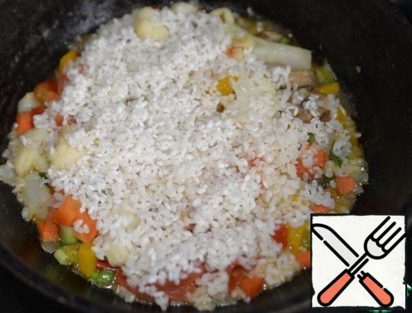 Take the rice, wash it. Evenly cover the top of the vegetables with rice.