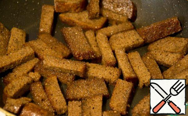 Borodinsky bread is cut into oblong pieces and fried in oil until it crunches.
