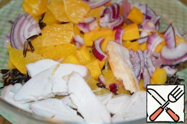 In a large bowl, add the cooled rice, chicken fillet, oranges, mango and onion.