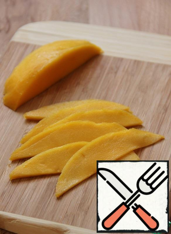 While the shrimps are being marinated, cut a quarter of the mango into thin slices.