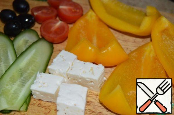 Cut the pepper into four parts, remove the seeds and stalk. Cut the tomatoes in half. Cut the feta or cheese into cubes. Can cut cut diagonally into thin long ovals.