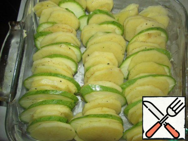 """Peel the potatoes, cut the potatoes and zucchini into round pieces, 0.5 cm thick, add salt and pepper, add nutmeg, crushed and chopped garlic without a central core, lubricate the refractory form with butter and put the """"packages"""" of potatoes and zucchini (see photo)"""