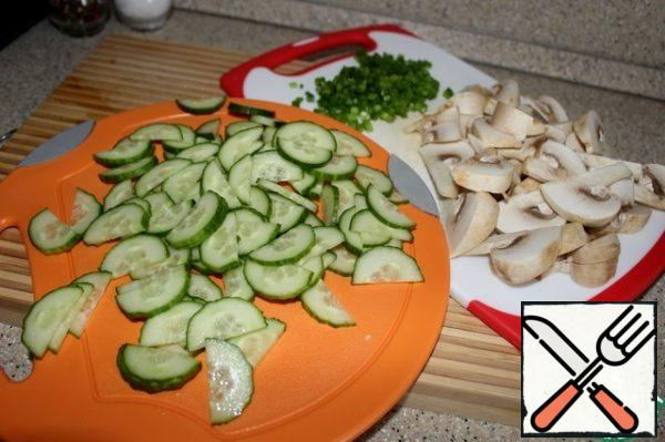Cut the cucumber lengthwise, then into thin slices, mushrooms-large slices, onions-finely.
