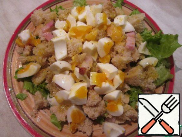 On the lettuce leaves, spread warm crackers with bacon, on top-coarsely chopped eggs, pour the remaining dressing. You can sprinkle with cheese. The salad is ready!
