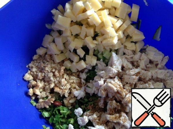 Cheese and boiled chicken breast cut into small cubes. Nuts are rolled with a rolling pin, not very finely. Add salt, adjika and hops-suneli.