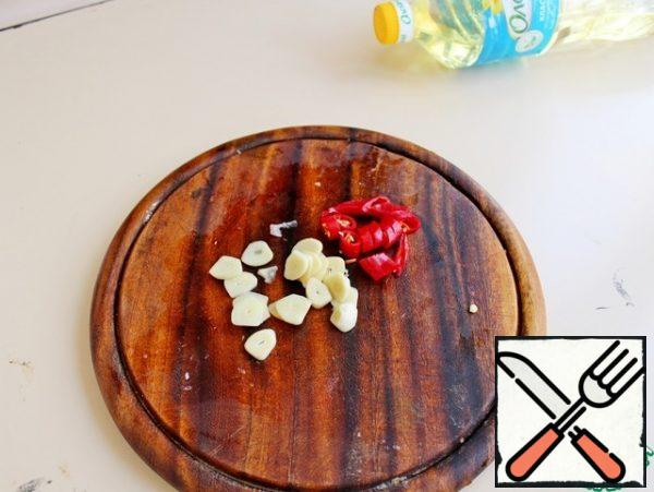 Chilli pepper and garlic cut into thin rings and add to the vegetables, fry for 1 min.