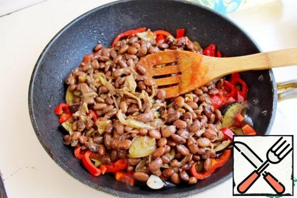 Add separately fried onions and mixed with red canned beans, cook for 2 minutes.