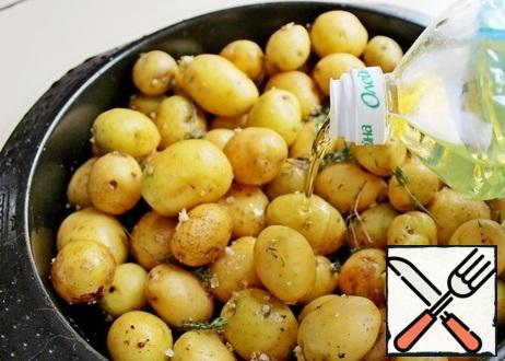 """Young small potatoes are well washed with a brush, dried, put in a mold, sprinkle with salt, thyme leaves and pour vegetable oil."""" Bake at 200 g for 30 minutes until tender."""