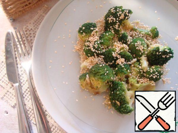 Broccoli spread on a plate, pour the dressing. She absorbed it well. Sprinkle with toasted sesame seeds.