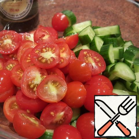 Cut the cherry tomatoes in half, cut the cucumbers into circles or halves, depending on the size. Place in a salad bowl.