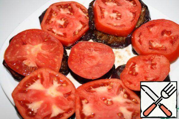 We put the eggplants on a plate or immediately on pieces with bread. Cut the tomato into pucks and put it on a circle of eggplant.