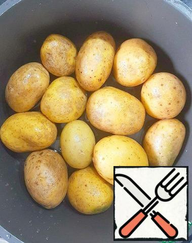 Choose potatoes of approximately the same size. Wash very well. Place in a saucepan with a thick bottom, or in a frying pan with high edges. Add water. Cover with a lid and put on a high heat. After boiling the water, reduce the heat to a minimum and leave the potatoes under the lid until tender (about 15-20 minutes). Periodically check with a toothpick whether the potatoes are ready. If the potatoes are ready, and the water is still left, then open the lid, make the heat to maximum and wait until the liquid completely evaporates.
