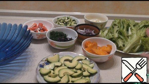 Cut the pitted avocado into half rings, sprinkle with lemon juice, and add salt. Cut the persimmon in half and cut into slices. Cut the cucumber crosswise, cut both parts into long strips. Cut the onion into half rings. Peel the quail eggs and cut each in half lengthwise. cut the crab sticks into slices about 2 cm thick.