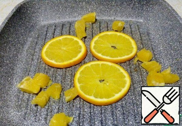 Brush the pan with oil, spread the rings and pieces of orange on it, warm it up, turning it over.