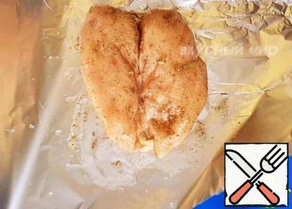 Put the chicken fillet on the foil, salt and pepper to taste, add the seasoning for the chicken, you can optionally paprika. Then add the vegetable oil and distribute it evenly. Wrap the foil, put it on a baking sheet and bake at a temperature of 200° for about 30-35 minutes.