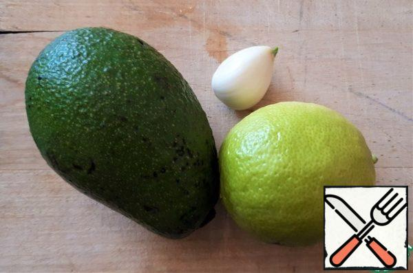 We prepare the products for the sauce. I need one avocado, but I have avocados, so I took two. Remove the pulp from the avocado with a spoon. Cut off half of the lime, along with the peel, the lime will go into a blender. Peel the garlic.